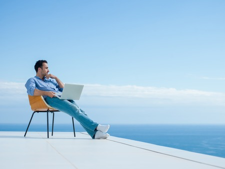 Photo pour handsome young man relaxing and working on laptop computer at home balcony while looking sunset - image libre de droit