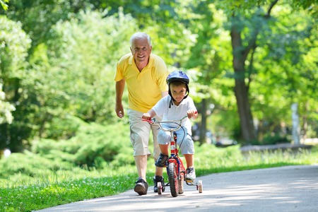 Photo pour happy grandfather and child have fun and play in park - image libre de droit