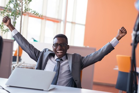 Photo pour Happy smiling successful African American businessman  in a suit in a modern bright office indoors - image libre de droit