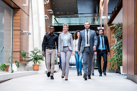 Foto de young multi ethnic business people group walking standing and top view - Imagen libre de derechos