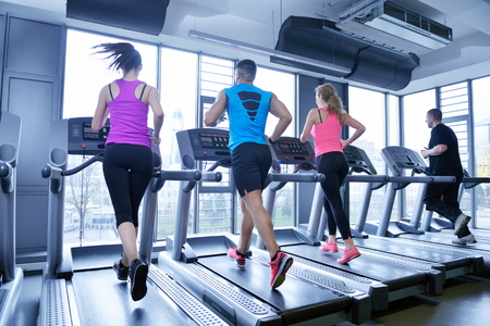 Foto de group of young people running on treadmills in modern sport  gym - Imagen libre de derechos