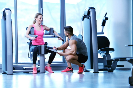 Foto de Gym woman exercising with her personal trainer - Imagen libre de derechos