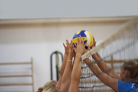 Foto de volleyball game sport with group of young beautiful girls indoor in sport arena school gym - Imagen libre de derechos