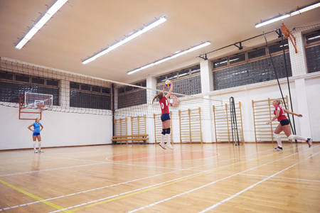 Foto per volleyball game sport with group of young beautiful  girls indoor in sport arena ball net - Immagine Royalty Free