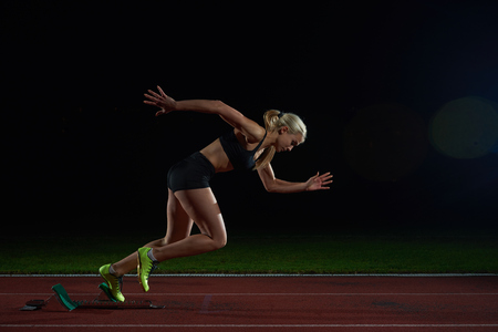 Photo pour woman  sprinter leaving starting blocks on the athletic  track. Side view. exploding start - image libre de droit