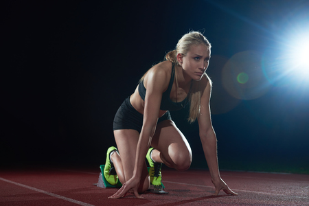 Photo for woman  sprinter leaving starting blocks on the athletic  track. Side view. exploding start - Royalty Free Image