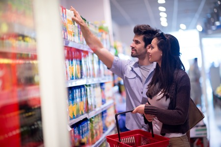 Photo pour Young couple shopping in a supermarket - image libre de droit