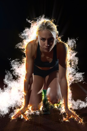 Photo for design with fire, smoke  and burm  of woman  sprinter leaving starting blocks on the athletic  track. Side view. exploding start - Royalty Free Image