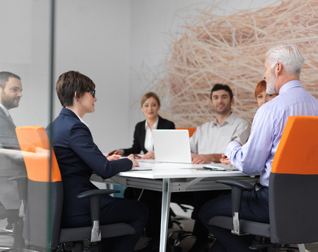 Foto de business people group on meeting at modern bright office indoors. Senior  businessman as leader in discussion. - Imagen libre de derechos