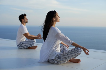 Foto de young couple practicing yoga at sunset in modern home terace with ocean and sunset in background - Imagen libre de derechos