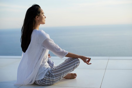 Foto de young woman practice yoga meditaion on sunset with ocean view in background - Imagen libre de derechos