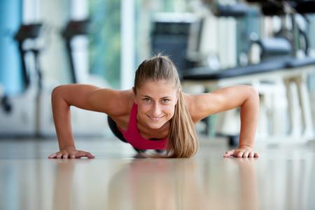 Foto de Gorgeous blonde woman warming up and doing some push ups a the gym - Imagen libre de derechos