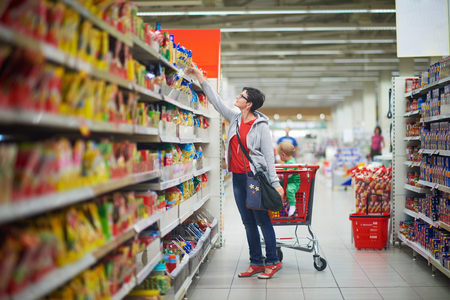 Photo pour young mother with baby in shopping mall supermarket store buying food and grocery - image libre de droit