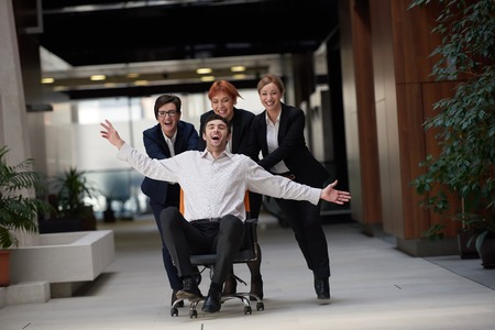 Foto de business people group at modern office indoors have fun and push office chair on corridor - Imagen libre de derechos