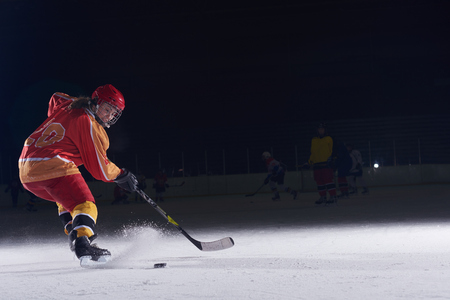 Photo pour teen girl children ice hockey player in action kicking puck with stick - image libre de droit