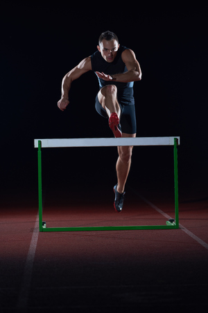 Photo pour man athlete jumping over a hurdles on athletics race track - image libre de droit