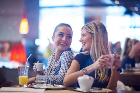 happy girl friends have cup of coffee in modern city restaurant