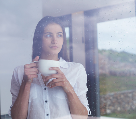 beautiful young woman drink first morning coffee at modern home interior with rain drops on big window door glass