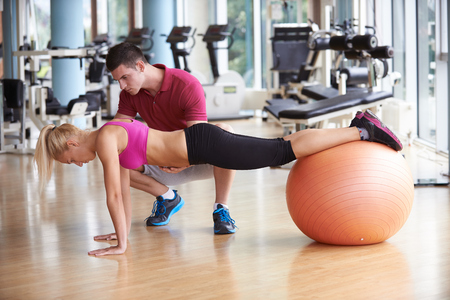 Foto de young sporty woman with trainer exercise in fitness gym - Imagen libre de derechos