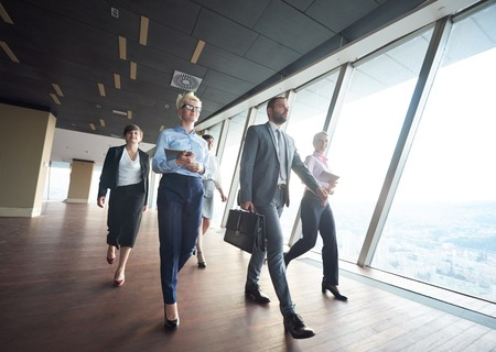 Foto de business team, businesspeople  group walking at modern bright office interior - Imagen libre de derechos
