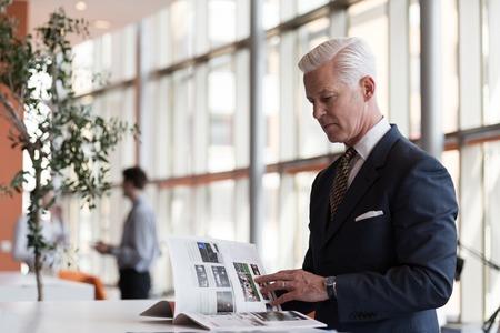 Photo pour senior business man reading magazine at modern bright office - image libre de droit