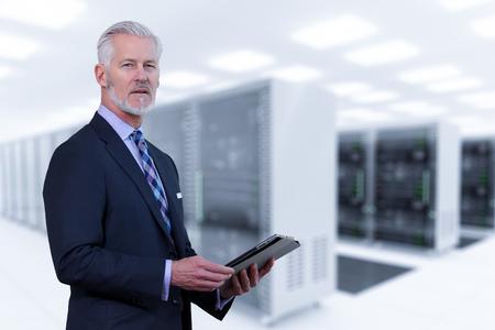 Photo pour Portrait of senior businessman in big rack server room - image libre de droit