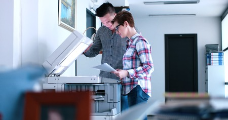 Photo pour Young Beautiful Woman with assistant Making Copies Of Files In The Copy Machine - image libre de droit