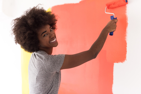 Foto de portrait of a young beautiful African American woman painting wall in her new apartment - Imagen libre de derechos