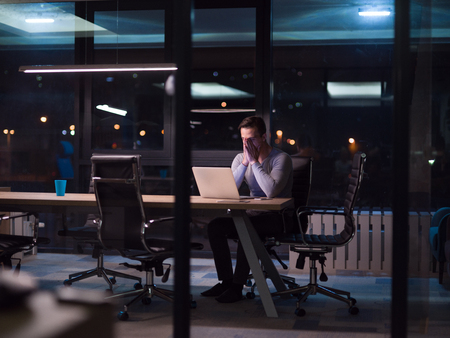 Foto de Young man working on laptop at night in dark office. The designer works in the later time. - Imagen libre de derechos