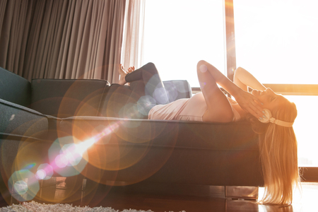 Photo pour woman listening to music with sun flare coming from window of apartment - image libre de droit