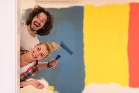 Photo for portrait of happy smiling young couple painting interior wall of new house  peeking from behind the wall - Royalty Free Image