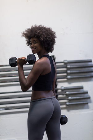 Photo pour young beautiful African American woman doing bicep curls in a gym - image libre de droit