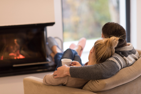 Photo pour Young romantic couple sitting on sofa in front of fireplace at home, looking at each other, talking and drinking coffee autumn day - image libre de droit