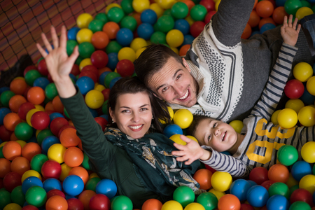 Foto de Happy young parents are playing with their kids at pool with colorful balls in a children's playroom - Imagen libre de derechos