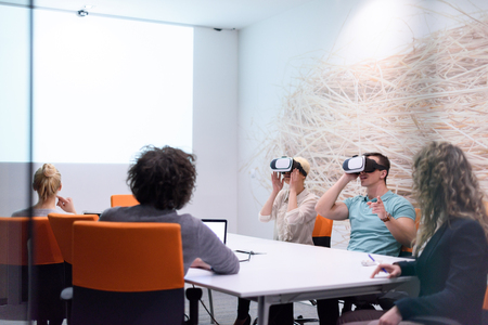 Foto de startup Business team using virtual reality headset in night office meeting  Developers meeting with virtual reality simulator around table in creative office. - Imagen libre de derechos