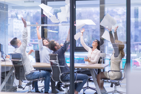 Photo for Group of young business people throwing documents and looking happy while celebrating success at their working places in startup office - Royalty Free Image