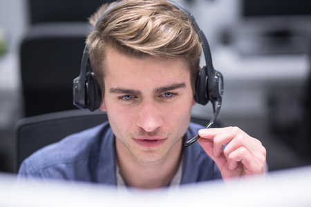 Photo pour young smiling male call centre operator doing his job with a headset - image libre de droit