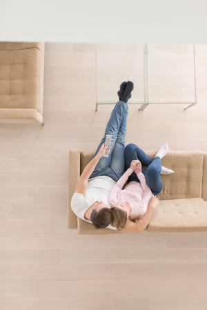 Foto de top view of Young couple on the sofa watching television together at home - Imagen libre de derechos