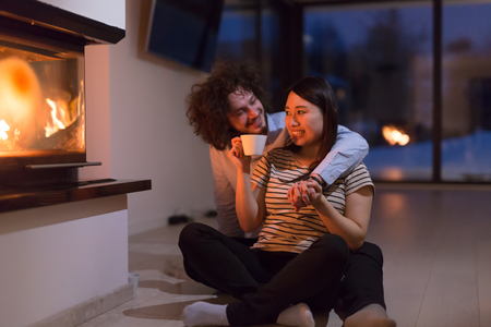 Photo for Young romantic multiethnic couple sitting on the floor in front of fireplace at home, talking and drinking tea on cold winter night - Royalty Free Image