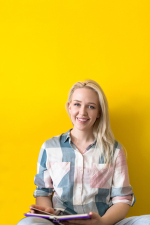 Foto de Young casual woman sitting on floor and reading a book, isolated on yellow background - Imagen libre de derechos