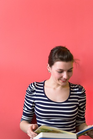 Foto de Young casual woman sitting on floor and reading a book, isolated on red background - Imagen libre de derechos