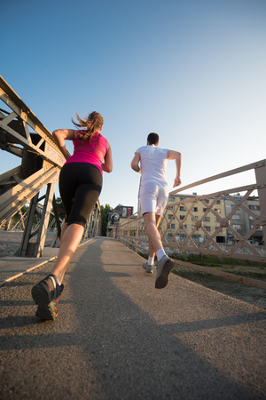 Photo pour urban sports, healthy young couple jogging across the bridge in the city at sunny morning - image libre de droit