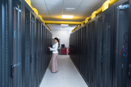 Foto de Female IT engineer working on a tablet computer in server room at modern data center - Imagen libre de derechos