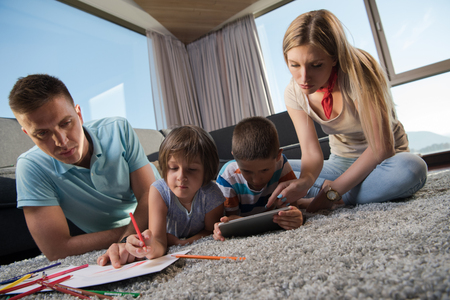 Photo pour Happy Young Family Playing Together at home on the floor using a tablet and a children's drawing set - image libre de droit