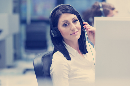 Photo pour young smiling female call centre operator doing her job with a headset - image libre de droit