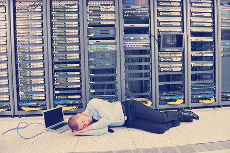 Photo pour it business man in network server room have problems and looking for  disaster situation  solution - image libre de droit