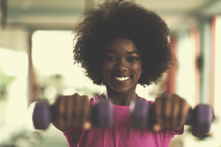 Photo pour happy healthy african american woman working out in a crossfit gym on weight loss with dumbbells - image libre de droit
