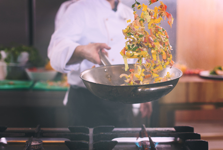 Foto de Young male chef flipping vegetables in wok at commercial kitchen - Imagen libre de derechos