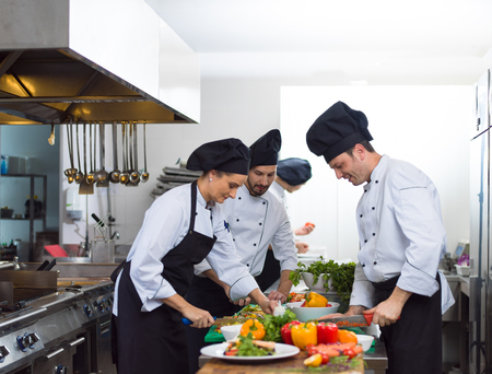 Foto de Professional team cooks and chefs preparing meals at busy hotel or restaurant  kitchen - Imagen libre de derechos