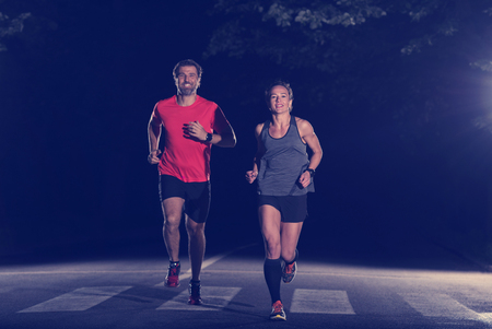 Foto de group of healthy people jogging in city park, runners team at night training - Imagen libre de derechos